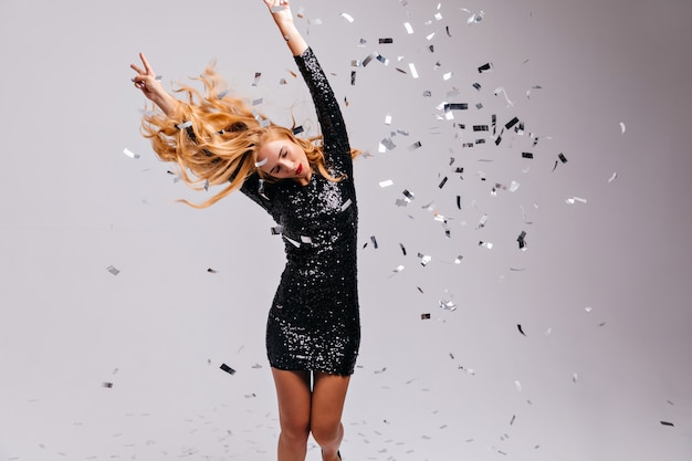 Zorgeloze blonde vrouw in zwarte jurk dansen onder confetti. verfijnd kaukasisch meisje dat pret heeft op feestje.