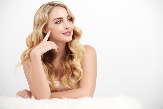 Zorgeloze blonde vrouw op wit