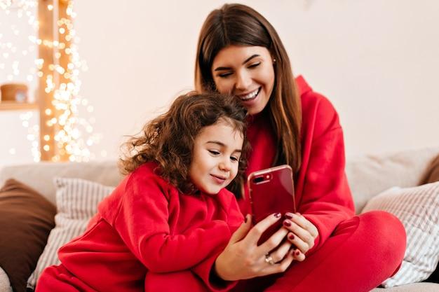 Zorgeloze brunette vrouw met dochter met behulp van smartphone. binnen schot van familie in rode kleren die op laag zitten.