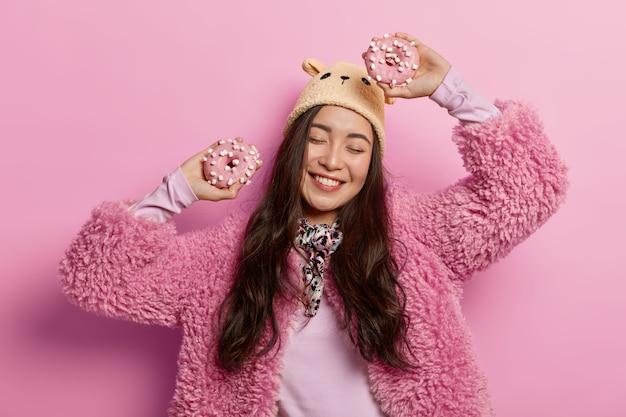 Zorgeloze dame danst vrolijk met twee zoete donuts, heeft plezier binnenshuis, draagt roze jas, bruine hoed