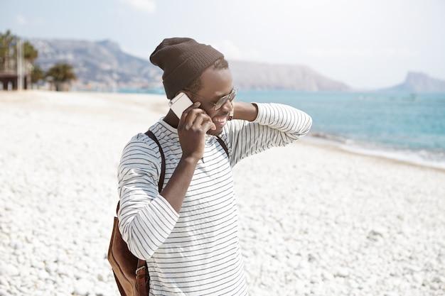 Zorgeloze donkere hipster in trendy kleding met een gesprek op smartphone tijdens een wandeling langs het kiezelstrand, ontspannen op een zomerdag aan zee