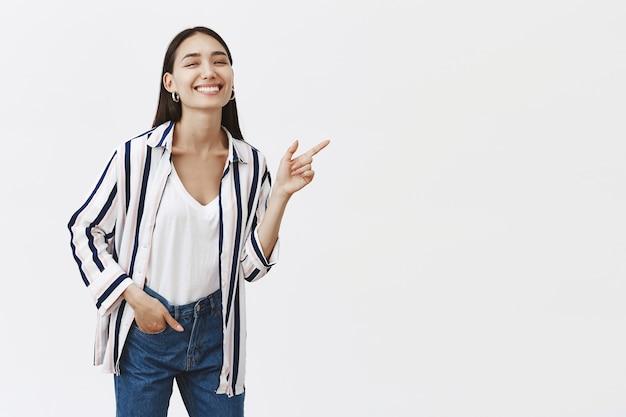 Zorgeloze emotionele en vriendelijke beroemde vrouw in stijlvolle gestreepte blouse, buigend en naar rechts wijzend met wijsvinger, hand in zak en breed glimlachend van geluk