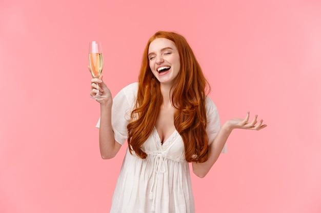 Zorgeloze en vrolijke aantrekkelijke roodharige vrouw viert gelegenheid, plezier op feest, ogen sluiten en lachen met opgeheven glas, champagne drinken, genieten van geweldig gezelschap, roze staan