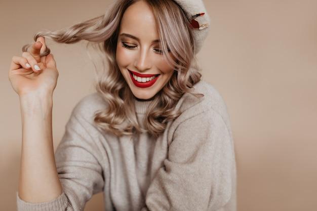 Zorgeloze franse vrouw in bruine trui genieten van fotoshoot