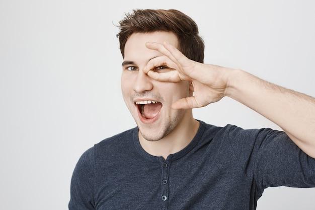 Zorgeloze gelukkige kerel die oke gebaar over oog toont en glimlachen