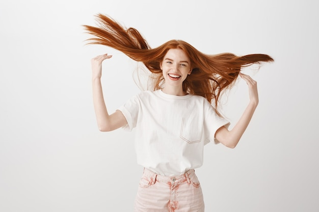 Zorgeloze gelukkige roodharige vrouw die haar haar gooit en vrolijk lacht
