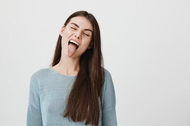 Zorgeloze gelukkige vrouw die dwaze tong toont