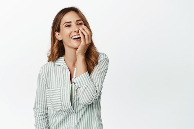 Zorgeloze gelukkige vrouw in blouse, lachend en vrolijk lachend, ontroerend gezicht en vrolijk naar voren kijkend