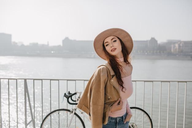 Zorgeloze gember vrouw in beige jas poseren in de buurt van fiets
