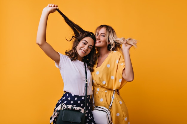 Zorgeloze goedgeklede meisjes die met hun haar spelen. europese dames poseren met een gelukkige oprechte glimlach.