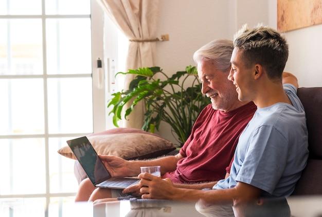 Zorgeloze grootvader en kleinzoon zitten samen op de bank thuis en kijken naar dezelfde laptop terwijl ze glimlachen - dezelfde interesse of passie delen. concept van verenigde familie en vriendschap