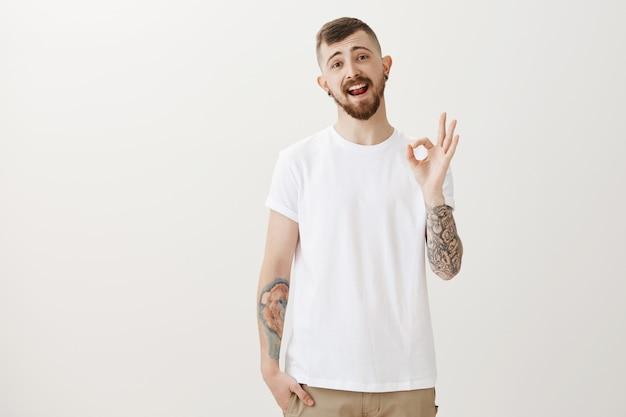 Zorgeloze hipster-man verzekert alles goed en toont een goed gebaar ontspannen