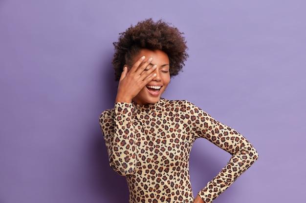 Zorgeloze jonge afro-amerikaanse vrouw bedekt gezicht met handpalm, sluit de ogen en giechelt positief, geniet van het leven