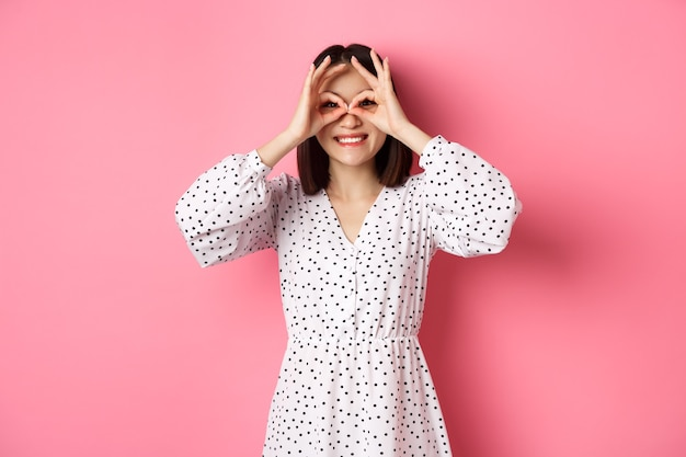 Zorgeloze jonge aziatische vrouw die door een handverrekijker naar de camera kijkt, naar kortingen staart, over een roze achtergrond staat.