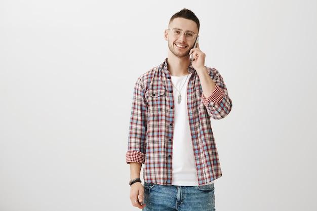 Zorgeloze jonge kerel poseren met zijn telefoon