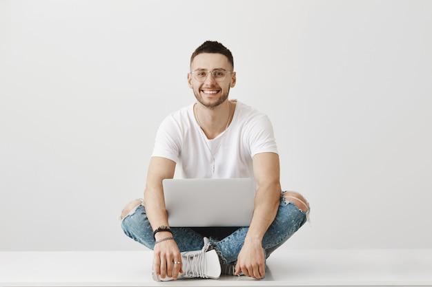 Zorgeloze jonge man met een bril poseren met zijn laptop
