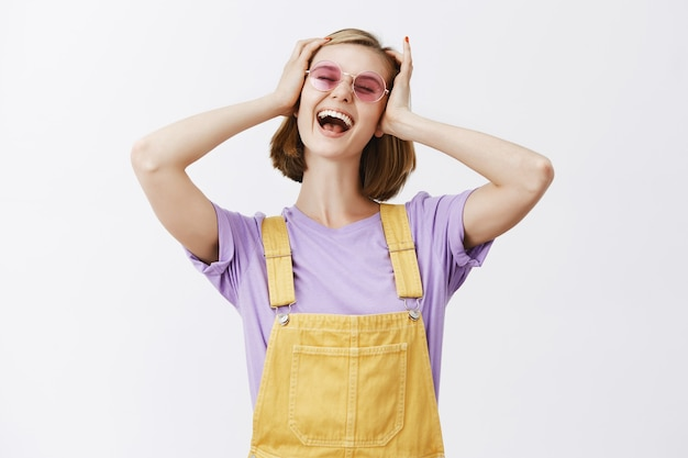 Zorgeloze jonge stijlvolle vrouw in zonnebril en zomerkleding opgewonden schreeuwen