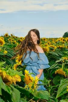 Zorgeloze jonge vrouw dansen in zonnebloemveld