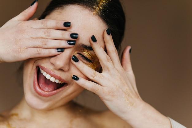 Zorgeloze jonge vrouw die met partijmake-up geluk uitdrukt. geïnspireerd donkerbruin meisje dat op donkere muur lacht.