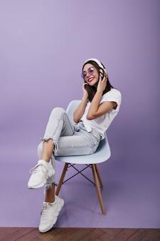 Zorgeloze jonge vrouw in trendy sneakers zittend op een stoel en muziek luisteren. modieus donkerbruin vrouwelijk model in hoofdtelefoons poseren.