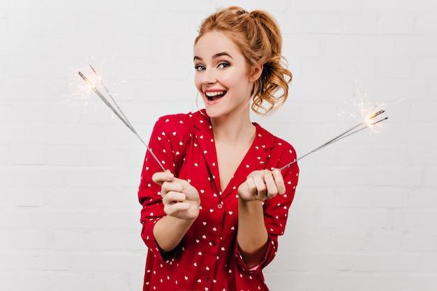 Zorgeloze jonge vrouw met trendy kapsel kerst vieren. grappig meisje in rode pyjama bengalen lichten op witte muur te houden