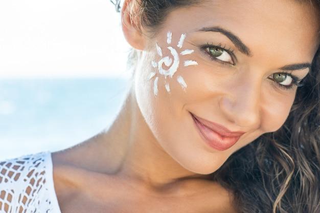 Zorgeloze jonge vrouw met zonnebrandcrème op gezicht bij strand