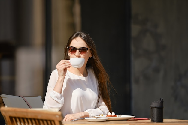 Zorgeloze jonge vrouw zittend op het terras van het café en cappuccino drinken
