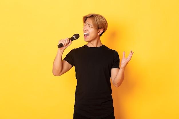 Zorgeloze knappe aziatische jongen, koreaanse zangeres zingen in microfoon met passie, staande gele muur