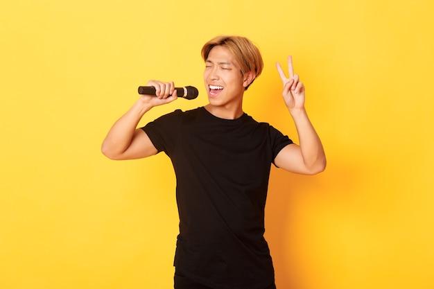 Zorgeloze knappe aziatische kerel die lied uitvoert