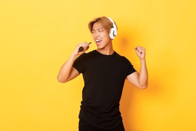 Zorgeloze knappe aziatische man in koptelefoon, karaoke-app spelen, zingen in de microfoon van de mobiele telefoon, staande gele muur