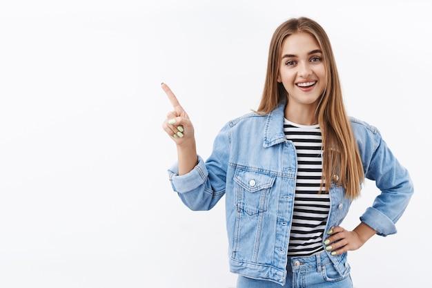 Zorgeloze knappe blonde vrouw die de linkerbovenhoek wijst en met de camera praat met een brede tevreden glimlach, geweldige plek aanbevelen, geweldige online winkel, vrolijk op een witte muur staan
