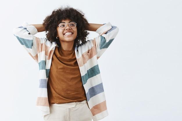 Zorgeloze knappe en stijlvolle vrouwelijke ondernemer in glazen hand in hand achter het hoofd in luie pose glimlachend vreugdevol en starend naar de rechterbovenhoek genieten van het leven en rust hebben