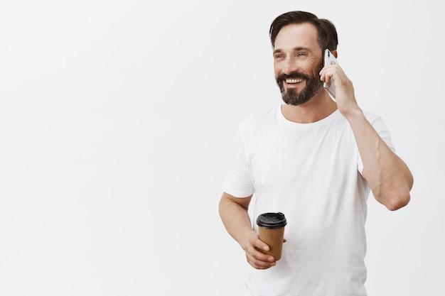 Zorgeloze knappe volwassen man koffie drinken en praten over smartphone