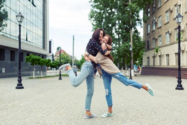Zorgeloze lachende zussen knuffelen en plezier samen