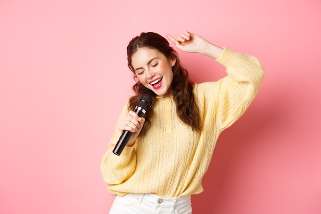 Zorgeloze moderne vrouw dansen en zingen lied in microfoon presteren met mic glimlachend en bewegend ontspannen staande tegen roze muur