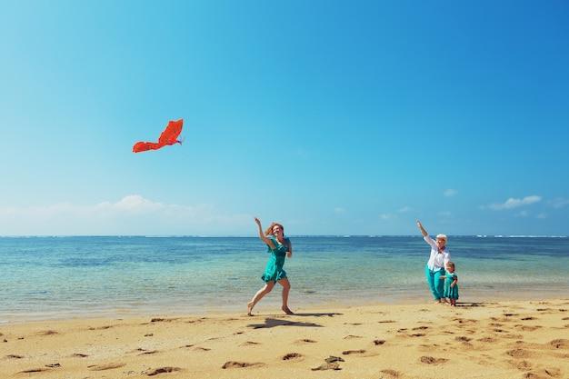 Zorgeloze moeder met vliegende rode vlieger door zee strand aan babymeisje en grootmoeder.