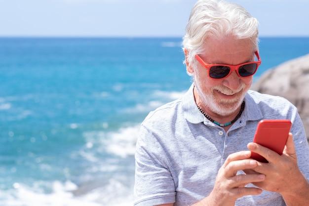 Zorgeloze mooie senior man met mobiele telefoon aan zee gelukkig pensioen vreugdevolle levensstijl