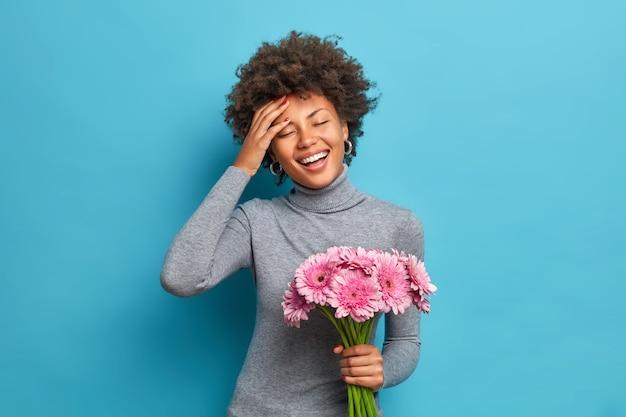 Zorgeloze optimistische donkere etnische vrouw houdt een boeket van mooie bloemen glimlacht breed