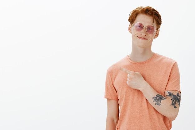 Zorgeloze roodharige man met zonnebril glimlachend, wijzend linker bovenhoek tevreden