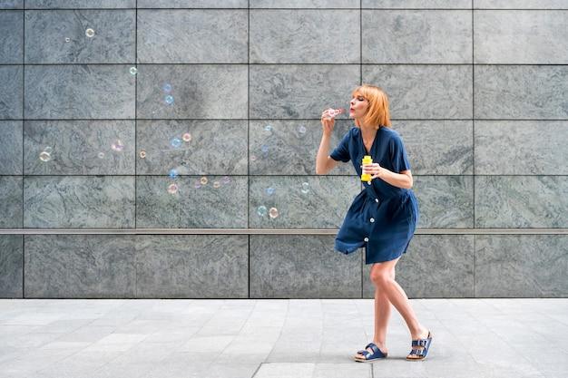 Zorgeloze roodharige vrouw die zeepbellen in de stad viert tegen een grijze muur van een commercieel gebouw op een winderige dag met copyspace
