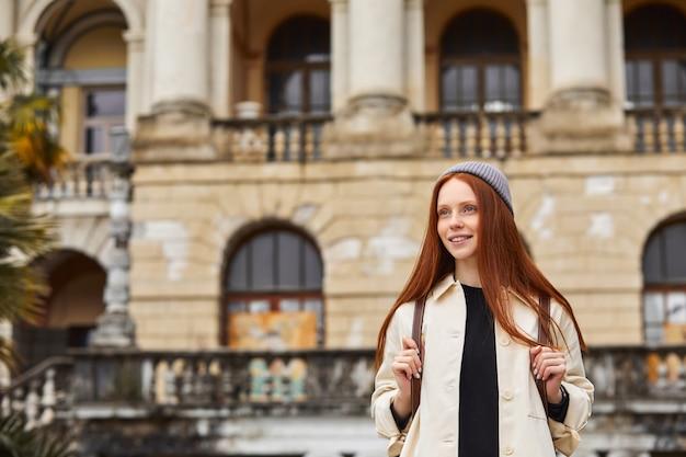 Zorgeloze roodharige vrouwelijke toerist loopt op oude sites excursies naar oude steden vrouwelijke tour...