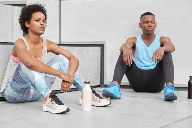 Zorgeloze, rustgevende zwarte zus en broer diep in gedachten, pauzeer na het joggen, draag casual comfortabele kleding, omringd met een fles gevuld met water om energie te hebben. jeugd- en sportconcept