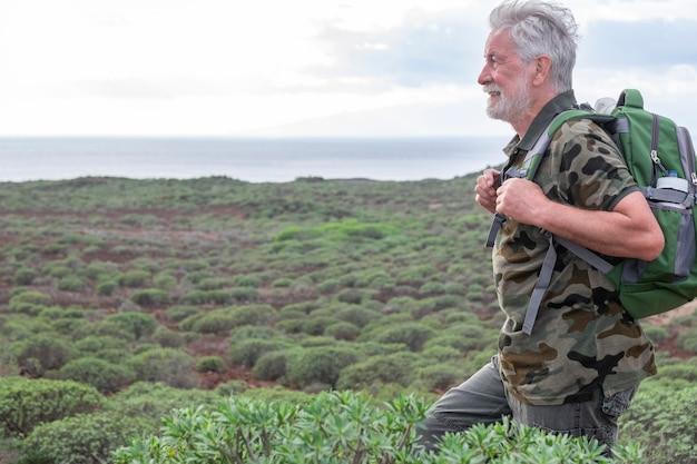 Zorgeloze senior man die geniet van een excursie in de buitenlucht tussen groene struiken en de zee glimlachend witharig