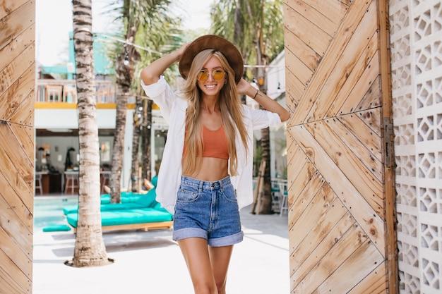 Zorgeloze slanke vrouw in trendy zomeroutfit poseren met schattige glimlach in het resort. romantische blonde vrouw in denim shorts en wit overhemd lachen tijdens buiten fotoshoot.