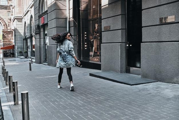 Zorgeloze stadsstijl. achteraanzicht van de volledige lengte van een jonge vrouw die over haar schouder kijkt