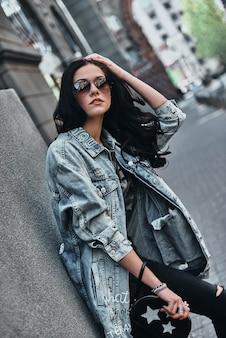 Zorgeloze stijl. mooie jonge vrouw in denim jasje camera kijken