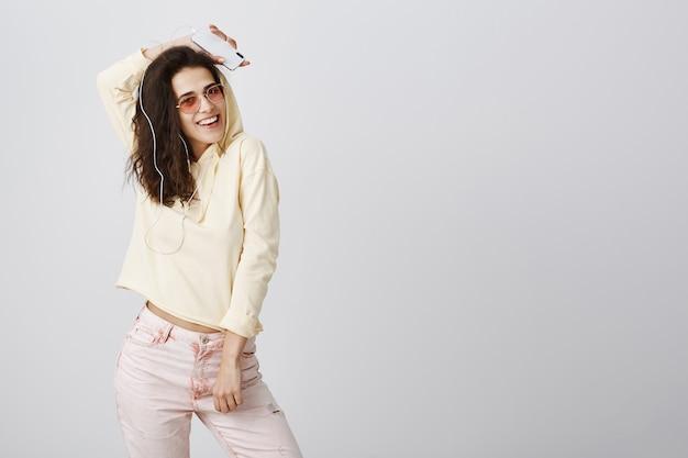 Zorgeloze stijlvolle vrouw muziek koptelefoon luisteren en dansen met mobiele telefoon