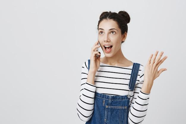 Zorgeloze tiener vrouw praten over de telefoon, gebaren