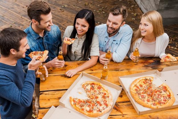 Zorgeloze tijd met vrienden. bovenaanzicht van vijf vrolijke mensen die flessen bier vasthouden en pizza eten terwijl ze buiten staan