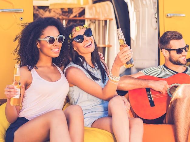 Zorgeloze tijd met vrienden. twee vrolijke jonge vrouwen die flessen bier vasthouden en glimlachen terwijl de man gitaar speelt met minibus op de achtergrond